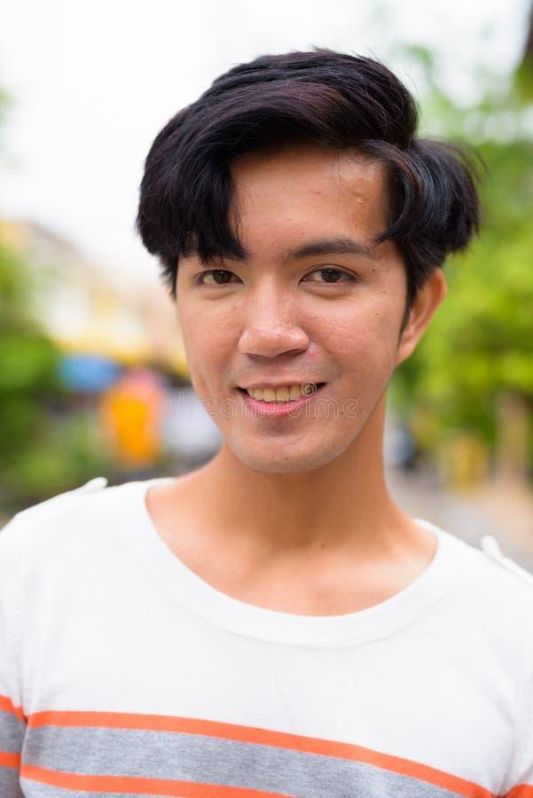 年轻英俊的亚裔在街上的男人户外 免版税库存照片