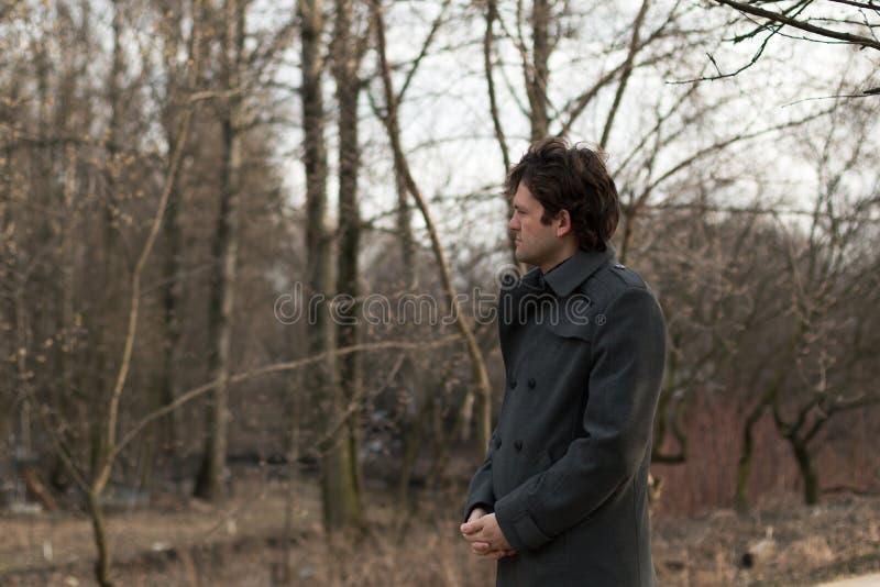 年轻英俊的人哀伤的画象朝左边看在公园、森林在秋天或春天 在自然的画象 免版税库存图片