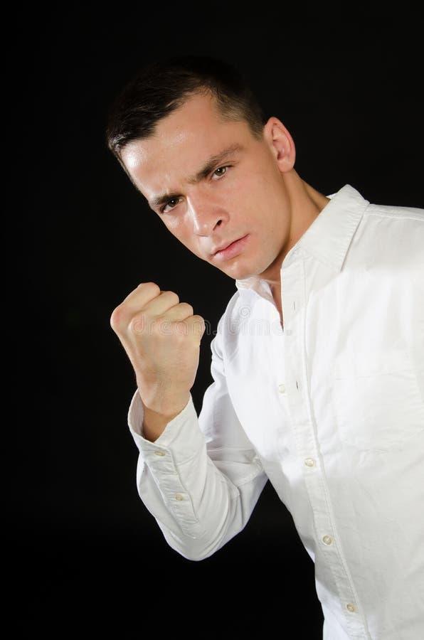 年轻英俊的人显示一个压缩的拳头 库存图片