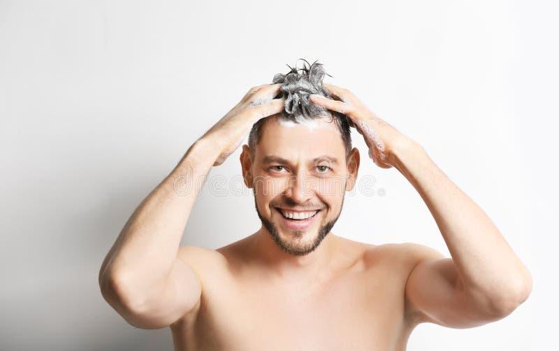 年轻英俊的人洗涤的头发 库存照片