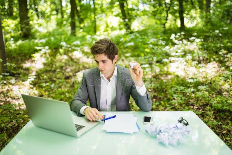 年轻英俊的商人在有膝上型计算机的工作表办公室在有感觉被用尽的恼怒的被弄皱的纸的绿色森林里和哀伤 库存照片