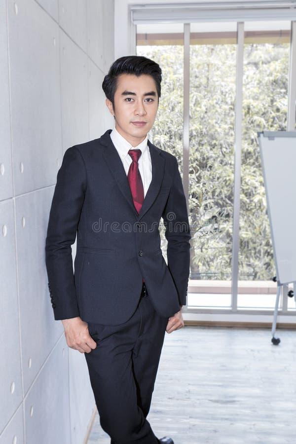 年轻英俊的商人微笑和聪明在办公室 他是20-30年 库存图片