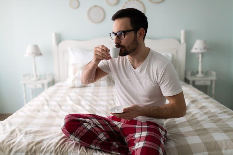 年轻英俊的在他的床上的人饮用的咖啡 免版税库存图片