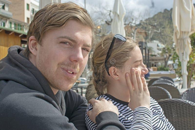 年轻英俊的夫妇在咖啡馆和半眯着的眼睛坐在纯然的阳光下 图库摄影