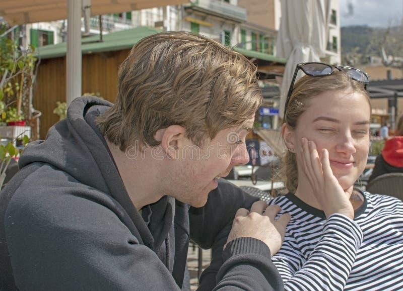 年轻英俊的夫妇在咖啡馆和半眯着的眼睛坐在纯然的阳光下 免版税库存照片