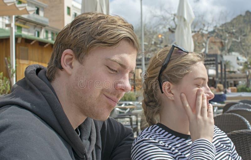 年轻英俊的夫妇在咖啡馆和半眯着的眼睛坐在纯然的阳光下 库存照片