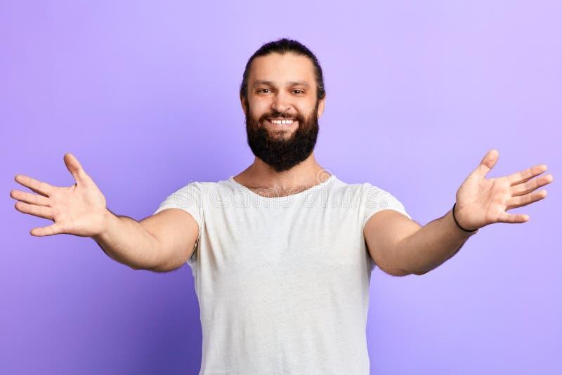 年轻英俊的快乐的招呼人佩带的白色T恤某人 免版税库存照片