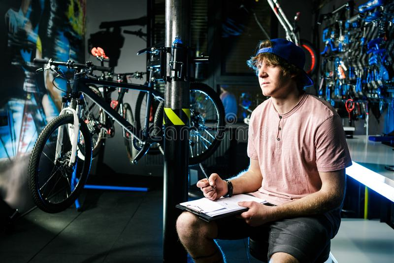 年轻英俊的时髦的人盖帽的和有卖自行车的纹身花刺小企业主的,车间坐
