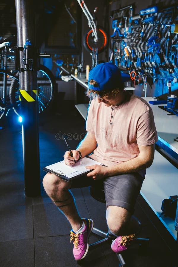 年轻英俊的时髦的人盖帽突然反弹的和有卖自行车的纹身花刺小企业主的,车间坐 免版税库存照片