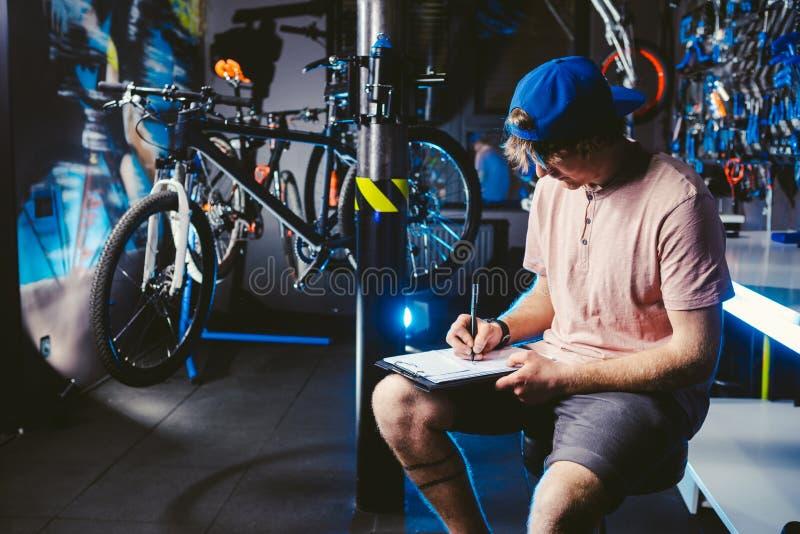 年轻英俊的时髦的人盖帽突然反弹的和有卖自行车的纹身花刺小企业主的,车间坐 免版税图库摄影