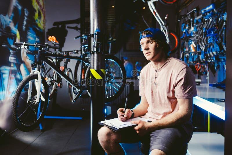 年轻英俊的时髦的人盖帽突然反弹的和有卖自行车的纹身花刺小企业主的,车间坐 免版税库存图片