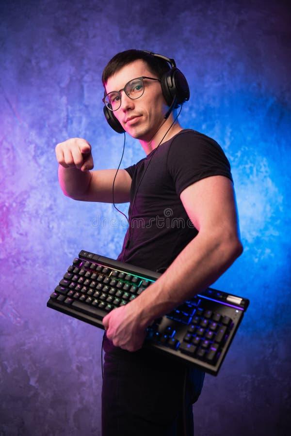 年轻英俊的有话筒的游戏玩家佩带的耳机,拿着键盘和把手指指向在霓虹的照相机色的 免版税库存图片