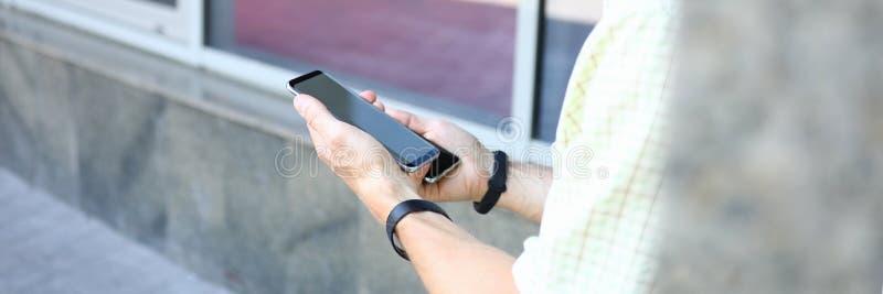 年轻英俊的男性在手上的拿着两个现代智能手机 免版税库存图片