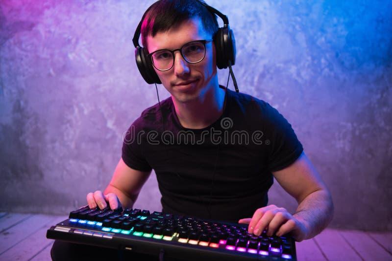 年轻英俊的赞成游戏玩家的画象坐与键盘的地板在霓虹色的室 库存图片