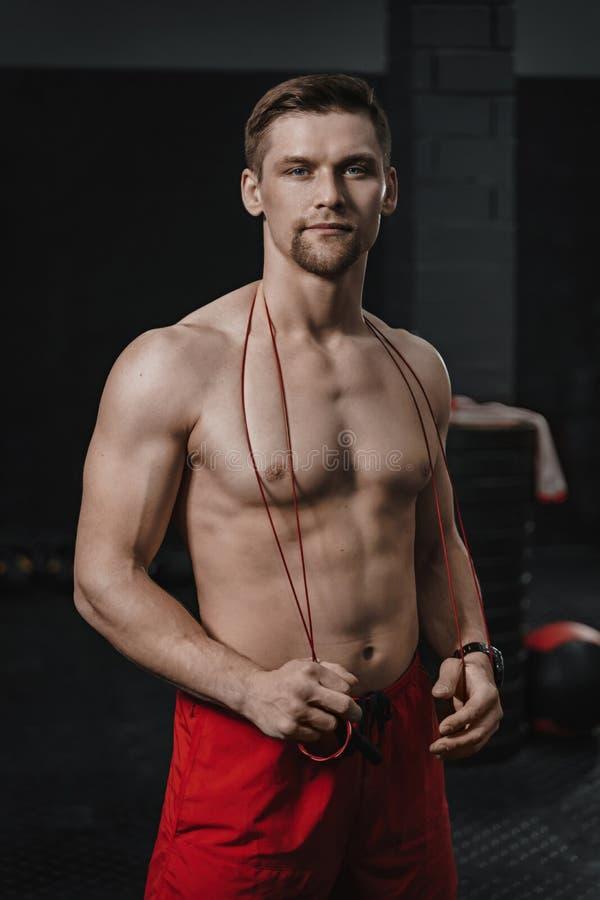 年轻英俊的赤裸上身的运动员垂直的被射击的画象crossfit健身房的 库存图片