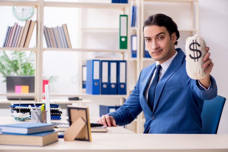 年轻英俊的雇员在办公室 库存照片