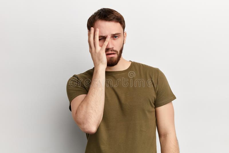年轻英俊的dissapointed不快乐的沮丧的人用在他的面孔的一只手 库存图片