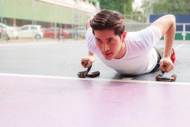 年轻英俊运动员人做在健身户外运动俱乐部增加 体育,锻炼,健康生活方式概念 免版税库存图片