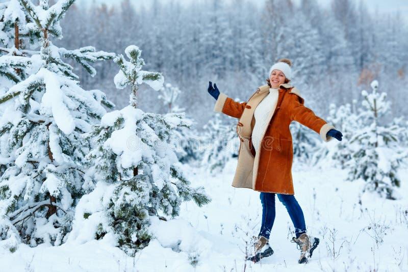 年轻获得孕妇佩带的衣服暖和在冬天森林的乐趣 免版税库存照片
