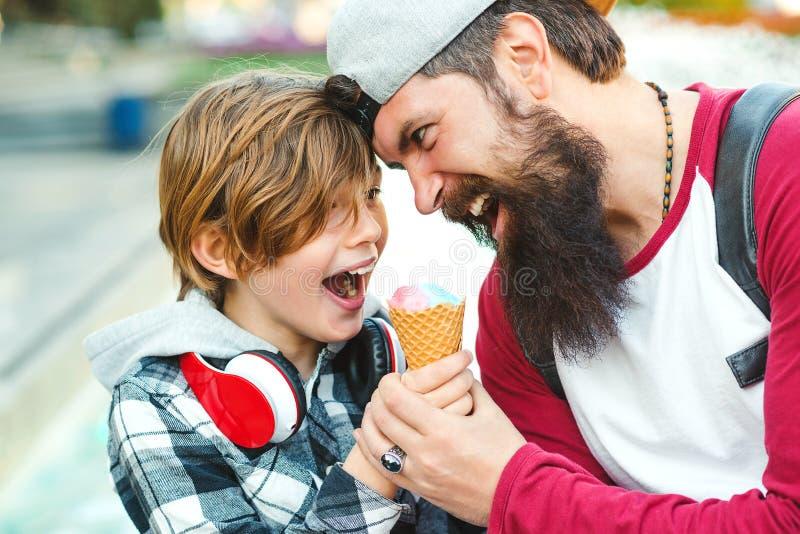 年轻获得父亲和的儿子一起享用冰淇凌和乐趣 愉快的情感家庭户外 假期,夏时,走在 免版税库存照片