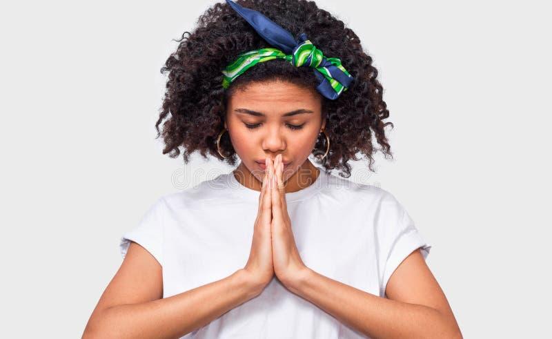 年轻蓬松卷发妇女的图象的水平的关闭在祈祷的姿态保留手 图库摄影
