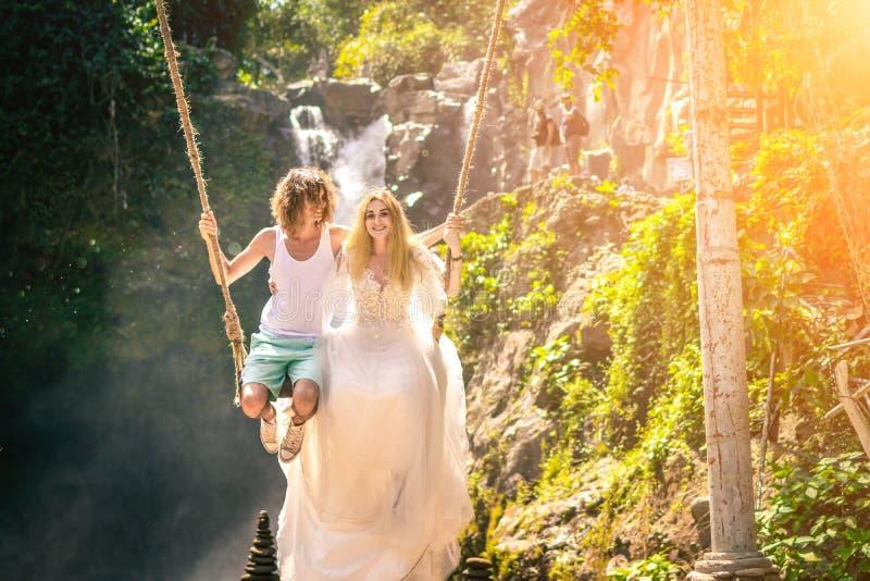 年轻蜜月夫妇在密林摇摆在湖,巴厘岛,印度尼西亚附近 免版税库存图片