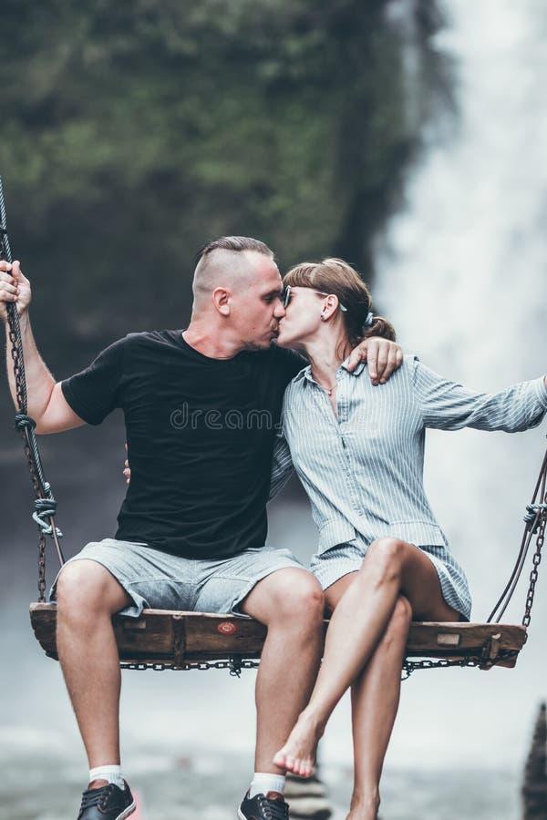 年轻蜜月夫妇在密林摇摆在瀑布,巴厘岛,印度尼西亚附近 Ubud 库存照片