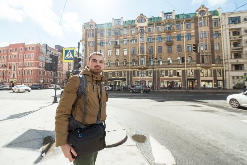 年轻行家人旅行的背包徒步旅行者室外在圣彼德堡街道 他是在交叉路旅行,远足概念 库存图片