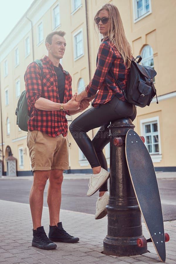 年轻行家夫妇,握手的英俊的溜冰者他的女朋友坐在一条老欧洲街道的一个消防龙头 免版税图库摄影
