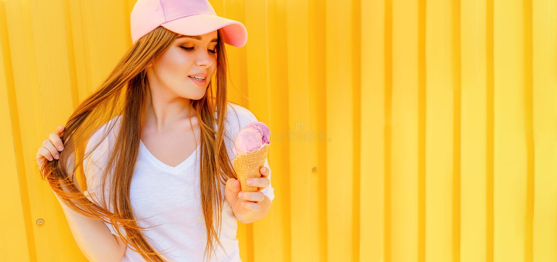 年轻行家女孩室外时尚画象用在黄色墙壁背景的冰淇凌 免版税库存图片