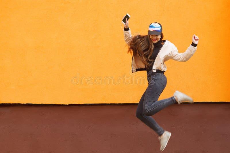 年轻行家女孩跳跃反对桔子和听到音乐由耳机由智能手机 都市的样式 库存照片