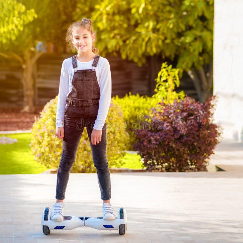 年轻行家少年女孩平衡在电翱翔委员会的,平衡电滑板晴朗的公园的双重轮子自已 库存图片