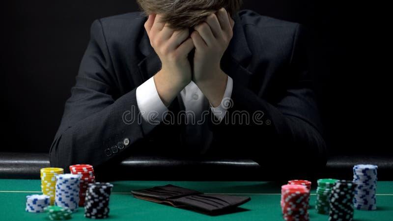 年轻被毁坏的在赌博娱乐场的商人丢失的扑克牌游戏,赌博的瘾 免版税库存照片