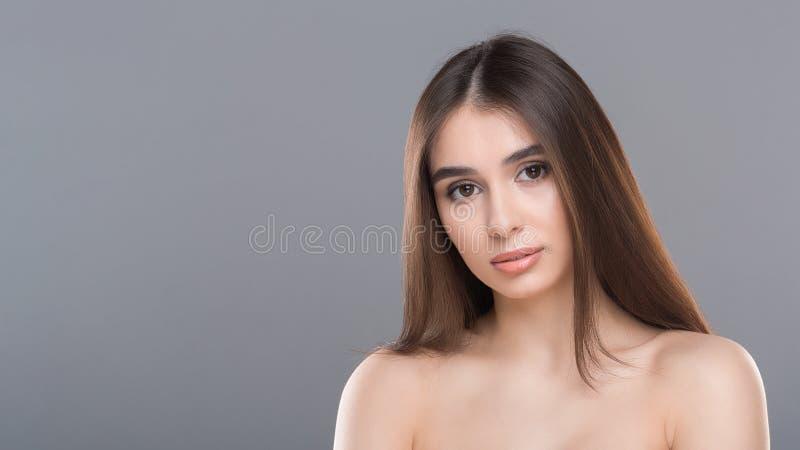 年轻裸体华美的妇女画象,灰色全景背景 免版税图库摄影