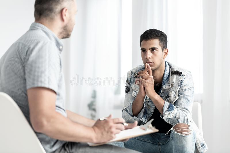 年轻西班牙人谈话与关于他的未来pla的一位心理学家 免版税图库摄影