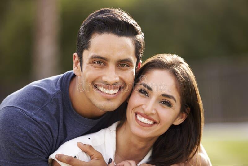 年轻西班牙夫妇看对照相机的微笑,关闭  免版税库存照片