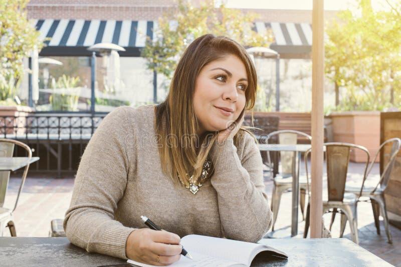 年轻西班牙妇女在学报户外愉快微笑写下她的生活目标 免版税库存图片