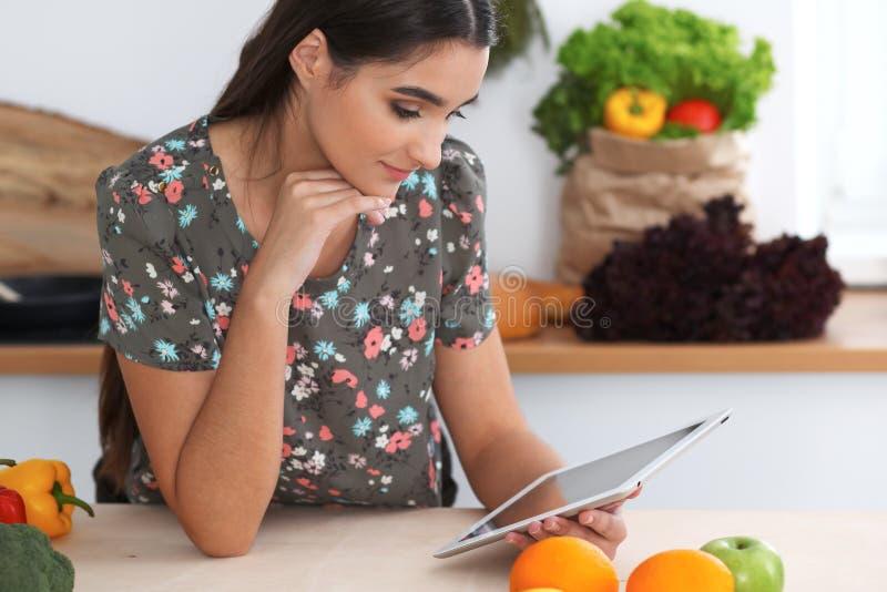 年轻西班牙妇女由片剂计算机和信用卡做网上购物 主妇被找到的新的食谱为 库存图片