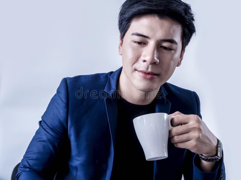 年轻认为一个项目的商人饮用的咖啡在候选会议地点 库存图片