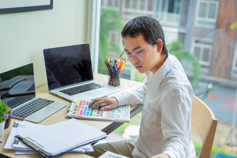 年轻设计师配合与选择的颜色样品一起使用在办公桌上 图库摄影