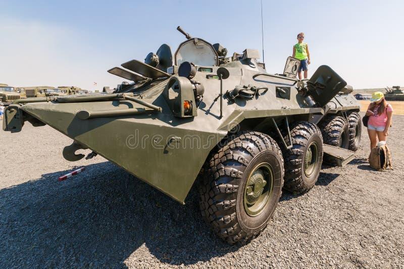 年轻访客站立装甲车BTR-82AM的关闭 免版税库存照片