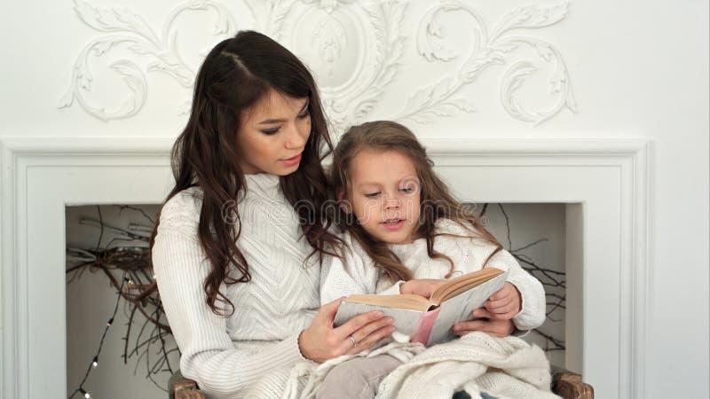 年轻读圣诞节传说的母亲和她的小女儿放松在扶手椅子由火地方 免版税图库摄影