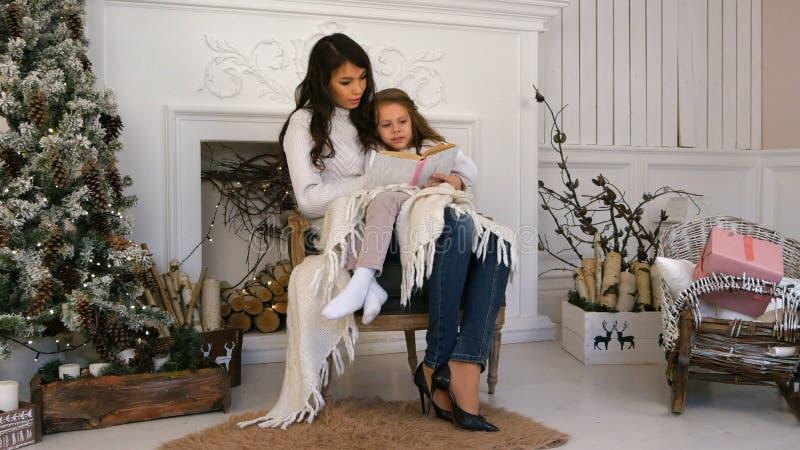 年轻读圣诞节传说的母亲和她的小女儿放松在扶手椅子由火地方 库存图片