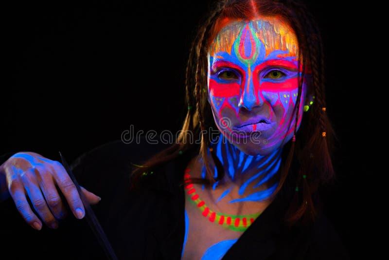 年轻赤裸大胆的bodyarted妇女特写镜头画象蓝色发光的紫外油漆和黄色目镜的 r 库存照片