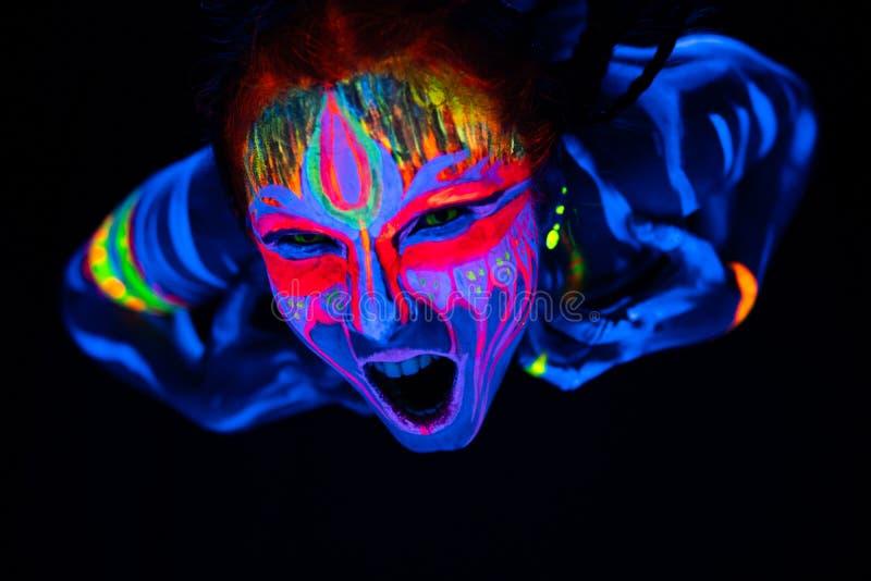 年轻赤裸bodyarted妇女特写镜头画象蓝色发光的紫外油漆和黄色目镜的 具体化个体 图库摄影