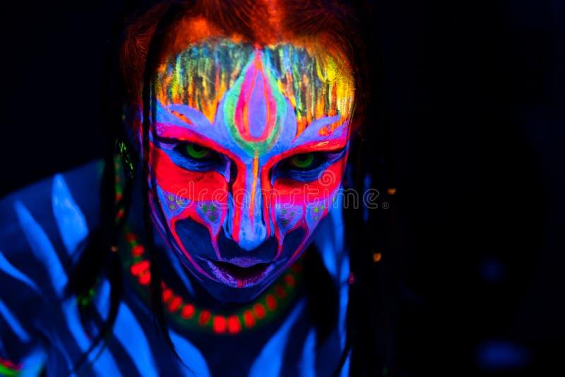 年轻赤裸bodyarted妇女特写镜头画象蓝色发光的紫外油漆和黄色目镜的 具体化个体 免版税库存图片