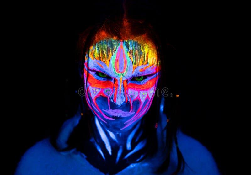 年轻赤裸bodyarted妇女特写镜头画象蓝色发光的紫外油漆和黄色目镜的 具体化个体 库存照片