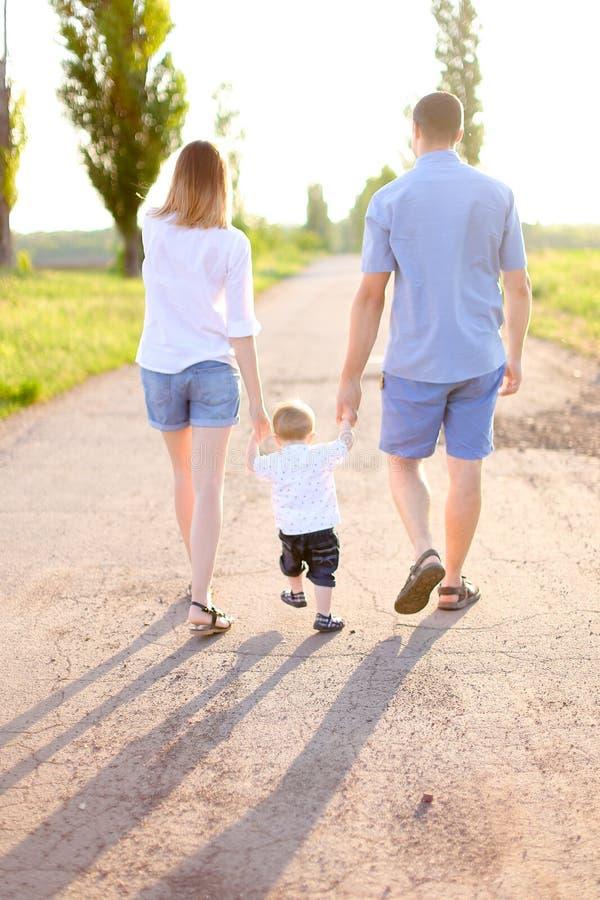 年轻走在有一点婴孩的路,阳光天气的母亲和父亲 免版税库存照片