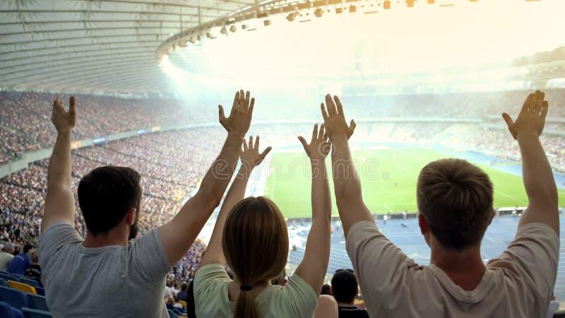 年轻足球迷用支持国家队的被举的手在比赛期间 库存照片