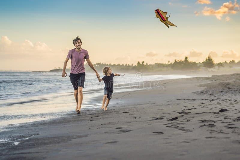 年轻跑与在海滩的风筝的父亲和他的儿子 库存照片